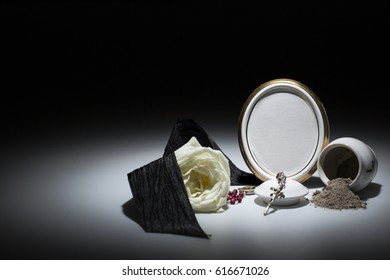 white urn with blank mourning frame, white rose, black tape, and rosary for sympathy card on dark background