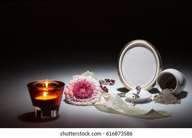 white urn with blank mourning frame, gerbera, white tape and rosary for sympathy card on dark background