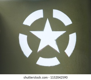 a white US army star in an invasion circle stenciled on an olive green painted military vehicle