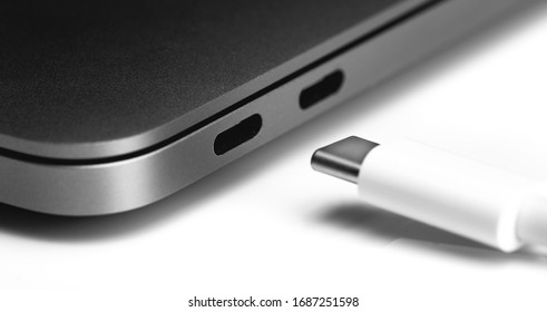 white USB Type-C cable with notebook USB C ports closeup on white table