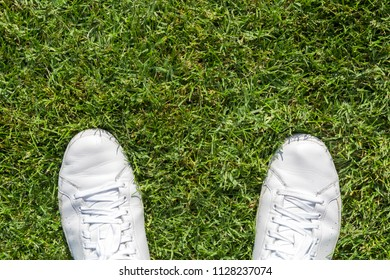 White used sneakers on a green grass.