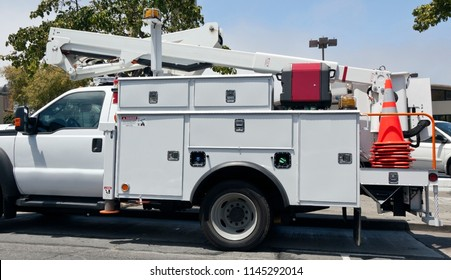 White utility truck with cherry picker parked in parking lot. Blue sky and tree background. Horizontal.