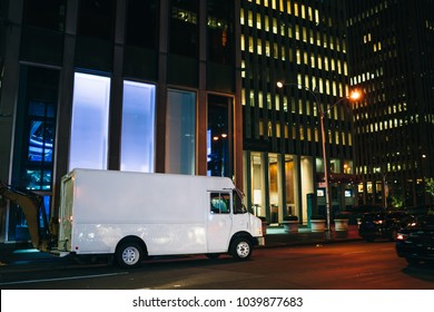 White van automobile delivery and transporting good for logistic service driving on road in evening megalopolis, blank truck body with copy space area for advertising or commerce information on street
