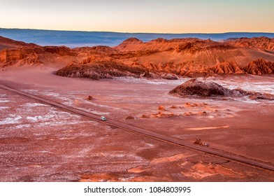 A white van crosses through a highway in a massive moon crater at Valle de la Luna, or the Moon Valley, Atacama desert, northern Chile, during sunset where rocky mountain appears golden.