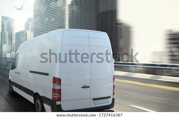 White van moving fast on the highway with a modern city in the background