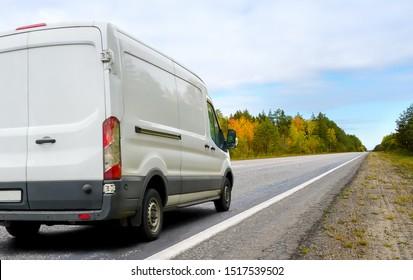 Weißer Lieferwagen auf Asphaltstraße auf Landschaftshintergrund im Herbst. Kleinlastwagen liefert die Waren