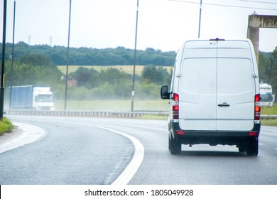 A 'white' van traveling along a main road in the United Kingdom, the roads wet and dirty.