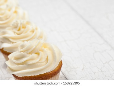 White vanilla cupcakes in a row. focus is on front cupcake.
