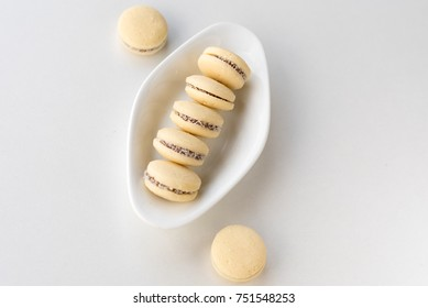 White vanilla macaroons on wooden background. French delicate dessert for Breakfast in the morning light.Delicious Argentinian cookies alfajores with cream on plate close-up on the table. Top view.