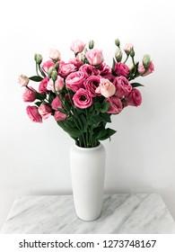 White Vase with Beautiful Eustoma flowers on Marble Table.