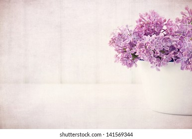 White vase with a bouquet of purple lilac spring flowers on vintage textured background