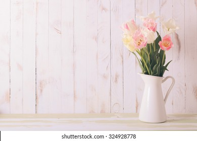 White vase with delicate shades armful of tulips on a wooden background