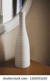 White vase with stripes texture on wooden table by round mirror