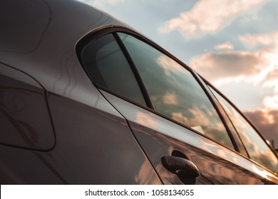 White vehicle car with reflection of sunset dramatic sky background. Beautiful color combination.