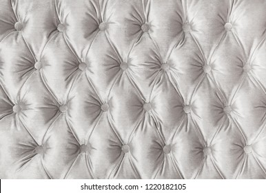 White velvet capitone textile background texture, retro Chesterfield style checkered soft tufted fabric furniture diamond pattern decoration with buttons, close up