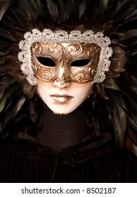 White venetian mask with black feathers in a traditional black costume