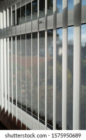 White vertical blinds slats hanging in front of double glazed white frame window. The slats have no cords at the bottom. The focus is shallow.