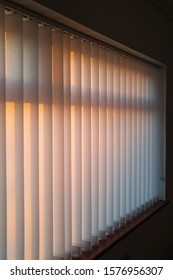 White vertical slat blinds hanging in front of a window as the sun is setting turning the light golden. The slats have sealed glued pockets and no cords at the bottom. Soft shallow focus