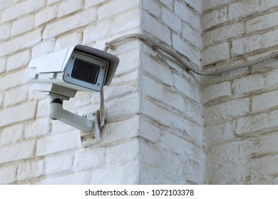 White video surveillance camera on the white dusty wall