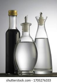 white vinegar and balsamic vinegar on wooden table against white background