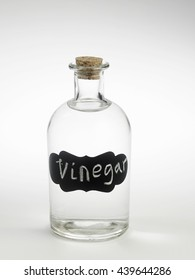 White vinegar in a glass bottle. White background.