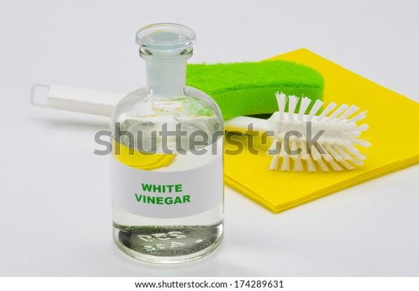 White vinegar in a glass bottle. White background. Organic cleaner.