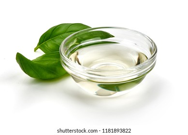 White Vinegar in a glass bowl with basil leaves, isolated on white background.