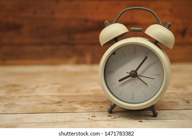 White vintage alarm clock on a rustic wooden table
