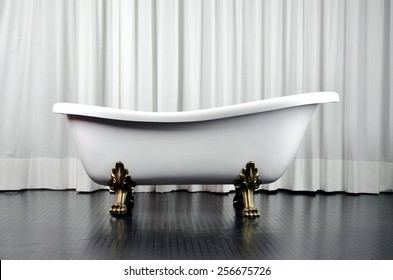 White vintage bath for luxurious bathrooms. Classical bathtub with feet of golden lion