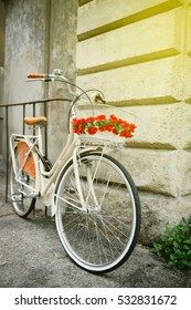 White vintage bicycle with red flowers parked against a wall in Pisa, Italy on a bright sunny day