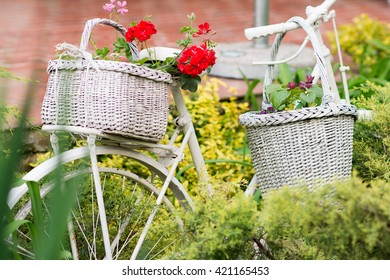 White vintage bicycle used for a garden decoration as a place for flowerpots and other objects. Useful and interesting ideas what to do with old bikes in garden,house or backyard.