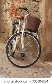 White vintage style bicycle leaning towards a rustic italian wall