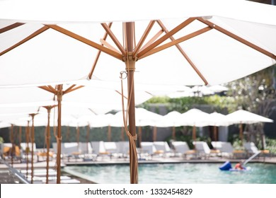 White vintage umbrella at the pool side with the comfortable bed cushion in the hotel resort.