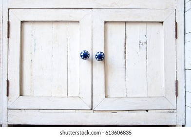 White vintage wooden cupboard with blue knobs