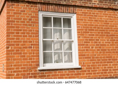 White vintage wooden window on a restored red brick wall