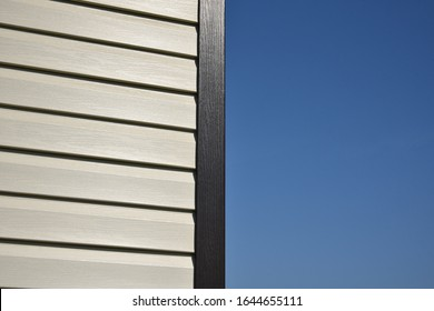 White vinyl siding wall surface with horizontal lines. texture of siding panels. Background for construction companies. Corner of a new residential private house. Blue sky background.