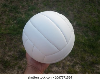 white volleyball held over green grass