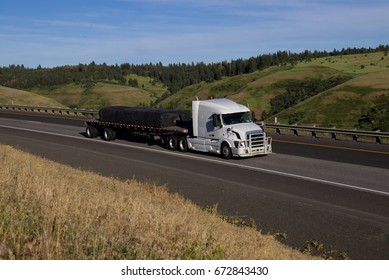 A White Volvo Semi-Truck pulling a loaded flat-bed trailer along a rural Oregon Highway.  June 20th, 2017 Rural Oregon, USA