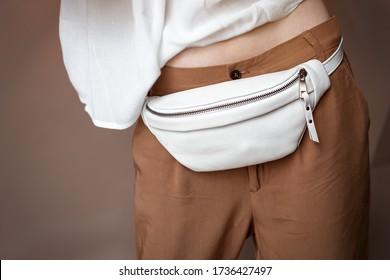 White waist bag on a model girl in brown trousers. Banana bag. Copy space for text