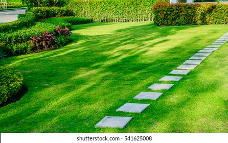 White walkway sheet in the garden, green grass with cement path  Contrasting with the bright green lawns and shrubs, shadows, trees, and morning sun Garden landscape design, lawn care service.