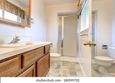 White wall bathroom with a wooden washbasin cabinet and glass door shower