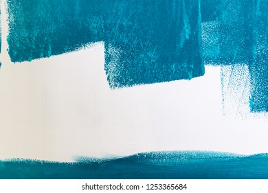 White wall being painted in blue or aqua or teal color. Background with copy space.