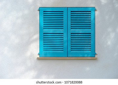 White wall with blue window shutter