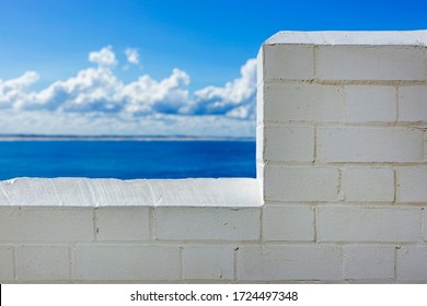 A White Wall Of Bricks With The Ocean On The Background