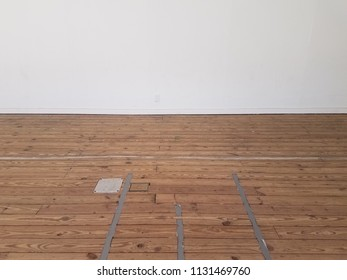 white wall and brown wood floor with tape on it