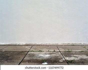 white wall with cement sidewalk