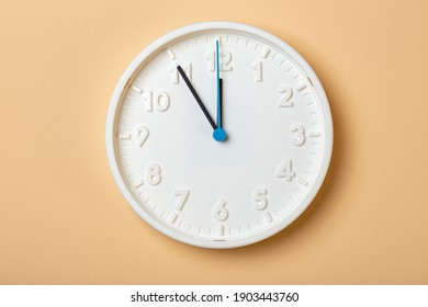 white wall clock with blue second hand show eleven o'clock
