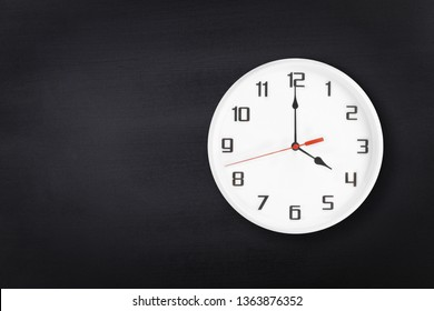 White wall clock on black chalkboard background. 4 a.m. or 4 p.m. Four o'clock
