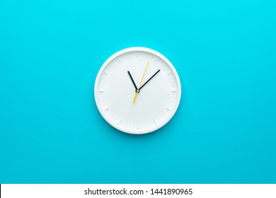 White wall clock with yellow second hand hanging on the wall. Minimalist flat lay image of plastic wall clock over blue turquiose background with copy space and central composition.
