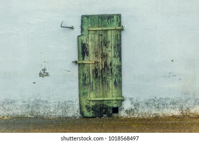 White wall with closed weathered door